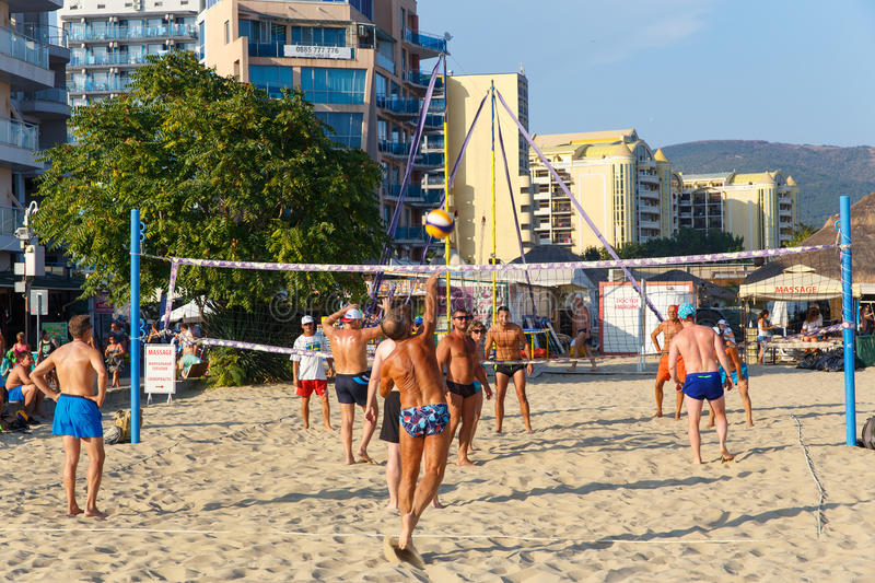 Active adults play the sport of volleyball on the sand beach stock image