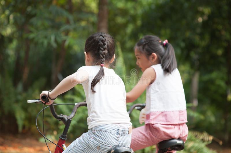 Active Asian children riding bike outdoor. Rear view of active Asian family at nature park. Children cycling outdoors. Morning sun flare background royalty free stock photos