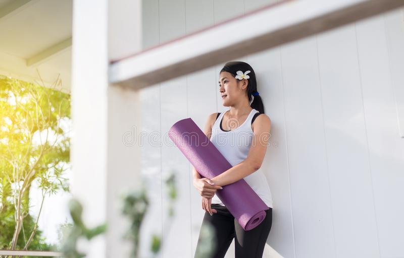 Active asian woman hands holding yoga mat after a workout,Exercise equipment,Happy and smiling,Healthy fitness and sport concept stock photography