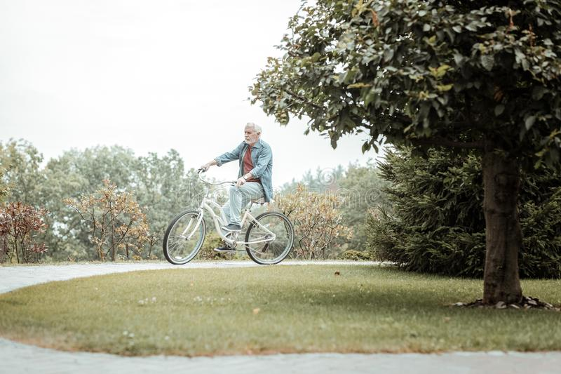 Active bearded retired man riding his bicycle stock photography