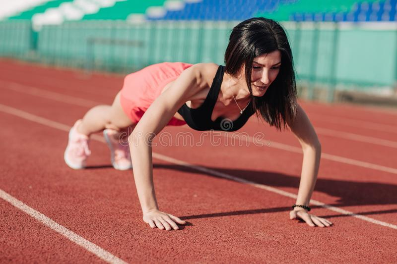 Active beautiful brunette woman in pink shorts and black top doing push ups at stadium.  royalty free stock images