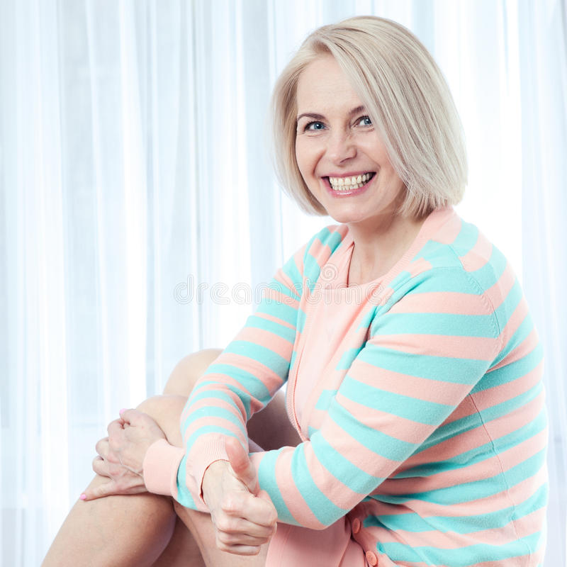 Active beautiful middle-aged woman smiling amiably, showing thumbs up and looking at the camera. royalty free stock photo