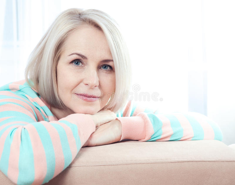 Active beautiful middle-aged woman smiling friendly and looking into the camera at home. Woman's face close up. stock photos