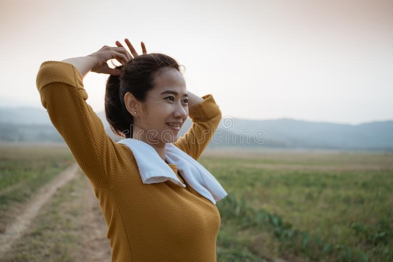 Active beautiful young woman tied her hair. While exercising outdoor royalty free stock photos