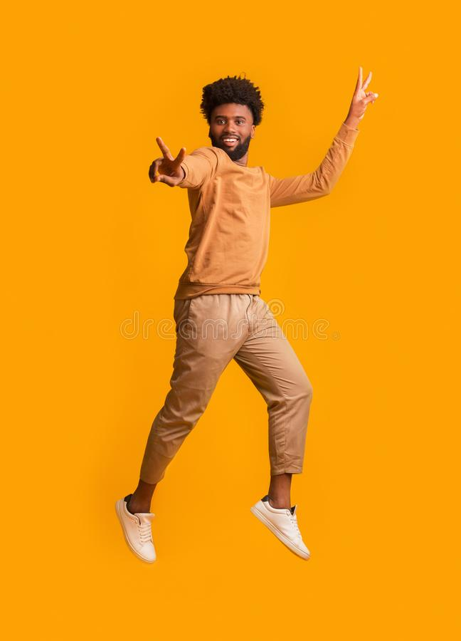 Active black man gesturing peace while jumping in the air royalty free stock images