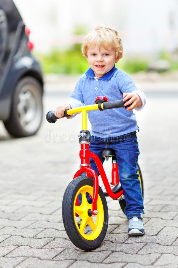 Active blond kid boy in colorful clothes driving balance and learner`s bike or bicycle in domestic garden. Toddler child stock images