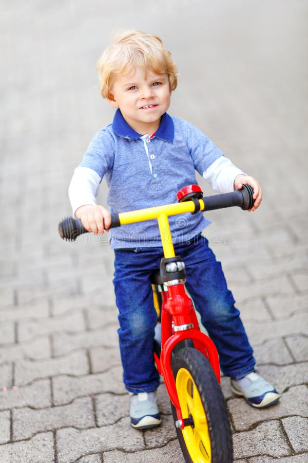Active blond kid boy in colorful clothes driving balance and learner`s bike or bicycle in domestic garden. Toddler child stock image