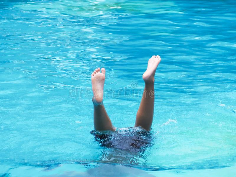 Active Boy diving and raising feet in the air at outdoor swimming pool royalty free stock photos