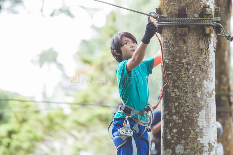 Active brave boy enjoying outbound climbing at adventure park on stock image