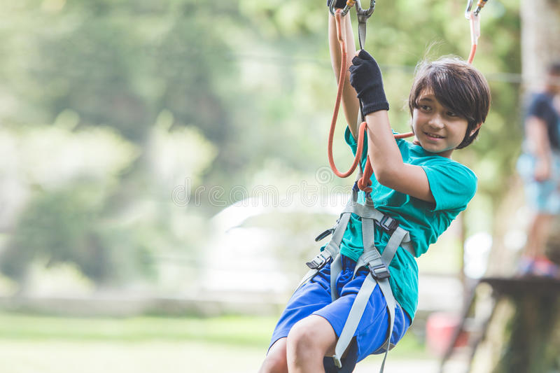 Active brave boy enjoying outbound climbing at adventure park on royalty free stock photography