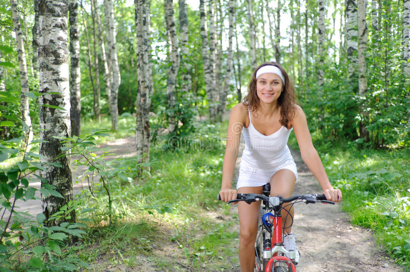 Active Brunette Woman On Red Bicycle Stock Photo