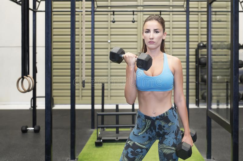 Active Caucasian female lifting heavy dumbbells, working out her arms at the gym stock image