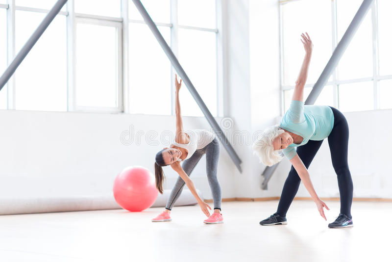 Active cheerful women exercising in a fitness club royalty free stock photo