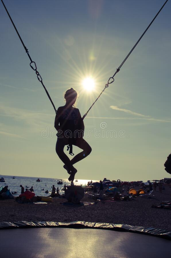 Active child in bungee jumping trampoline at sunset. Silhouette of girl enjoying adrenaline sporty activity in bungee jumping construction at the seaside stock photo