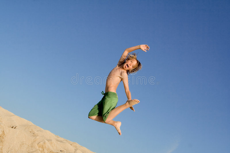 Active child jumping on vacation. Happy active kid jumping for joy on summer beach vacation stock photo