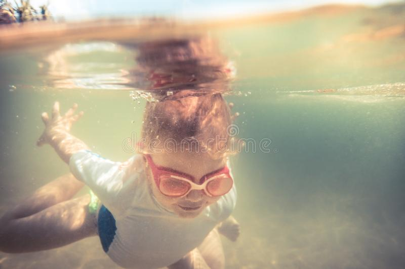 Child toddler swimming underwater during summer beach holidays vacation royalty free stock photography