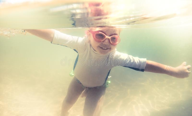 Active child toddler swimming underwater during summer beach holidays vacation stock photography