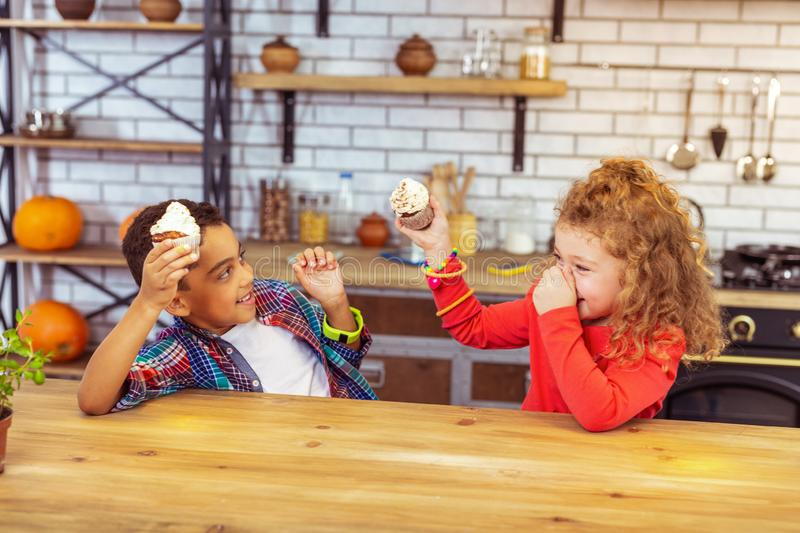 Active children going to fight with cakes. Be careful. Delighted brunette boy expressing positivity while looking at his friend royalty free stock image