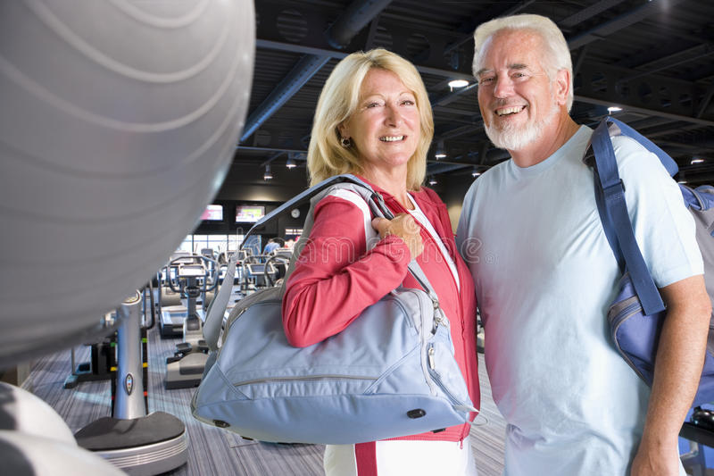 Active couple carrying gym bags in health club royalty free stock photos