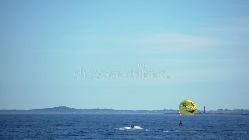 Active couple parasailing, smiley parachute flying above sea surface, good mood royalty free stock images