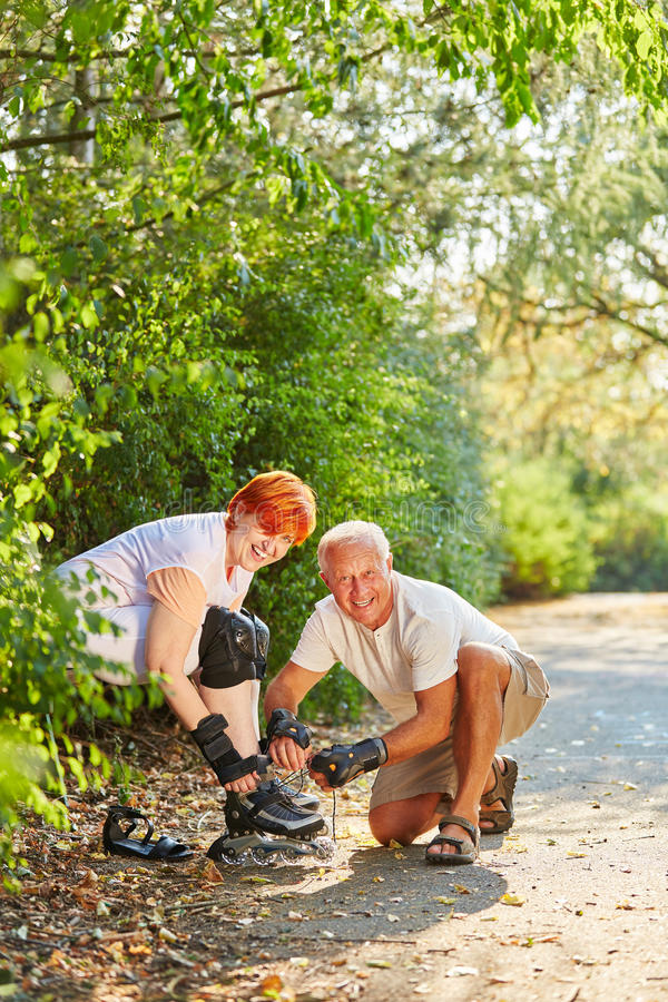 Active couple of seniors getting ready to skate. In the park in summer royalty free stock photos