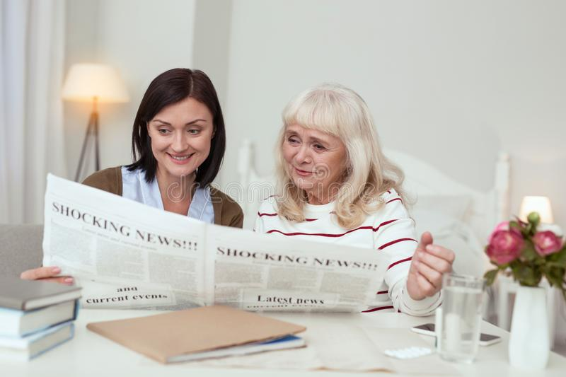 Active elder woman and caregiver reading newspaper. News in world. Satisfied elder women and caregiver reading news and smiling stock image