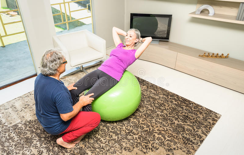 Active elderly couple at fitness training with swiss ball at home stock images