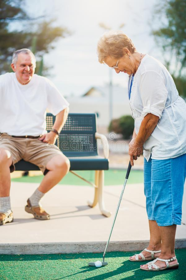 Active elderly senior couple playing miniature golf together stock photos