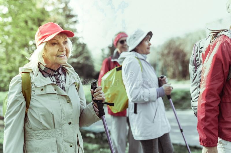 Active elderly woman hiking with her friends royalty free stock image