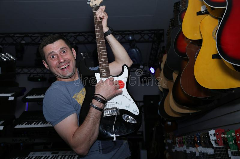 Active emotional with a smile on his face a young man playing an electric guitar against the background of guitars in a soft blur stock photography