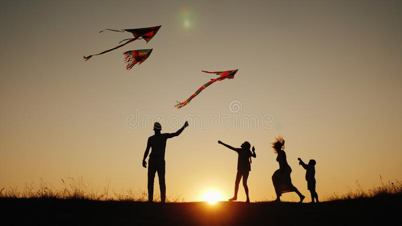 Active family with children launches kites in a picturesque place at sunset stock photography