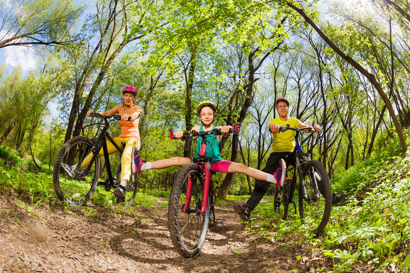 Active family cycling down the woods trail. Active family, mother, father and teenage girl having fun cycling down the woods trail in the spring time stock photo