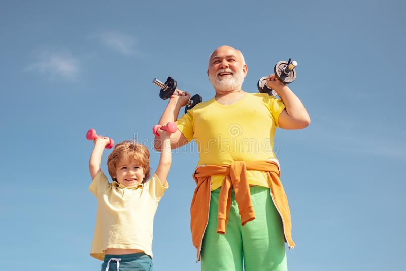Active family enjoy sport and fitness. Funny old senior man and kid boy with dumbbells. Grandfather and child do morning stock photos