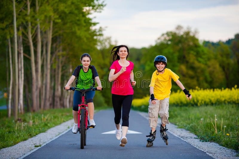 Active family - mother and kids running, biking, rollerblading royalty free stock photography