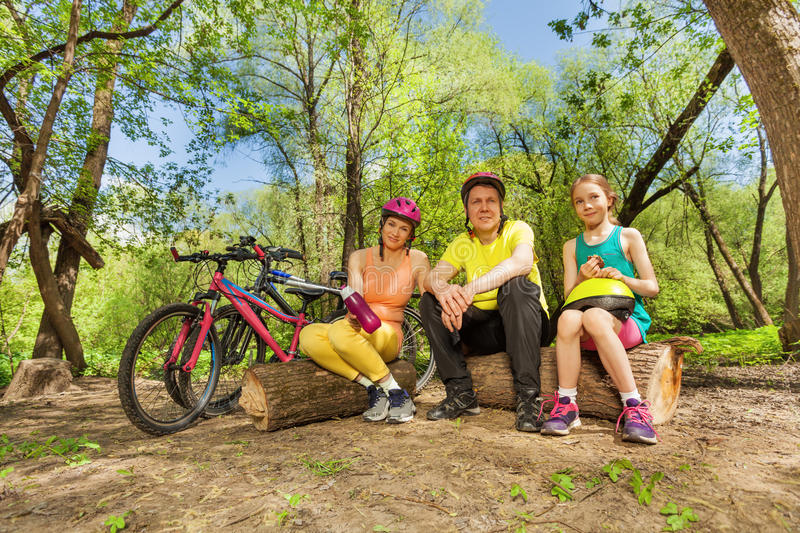 Active family resting on the logs after cycling. Active family resting and making pause on a log in the sunny spring wood, tired after cycling royalty free stock photography