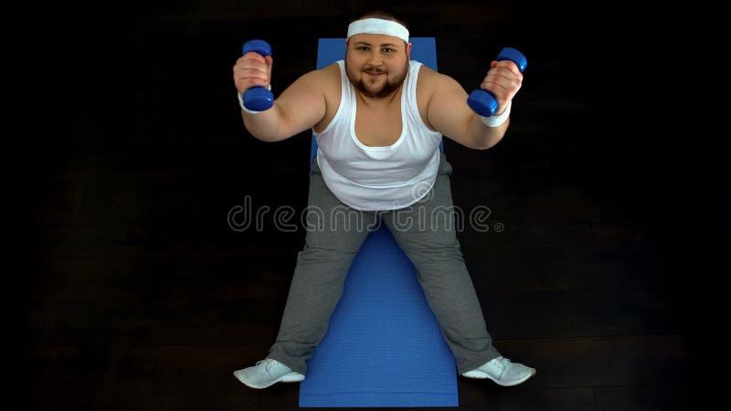 Active fat man lifting dumbbells sitting on mat, sport motivation, discipline royalty free stock photo