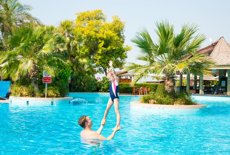 Active father teaching his kid daughter to swim in pool on tropical resort. Summer vacations and sport concept. Active father teaching his kid daughter to swim royalty free stock photography