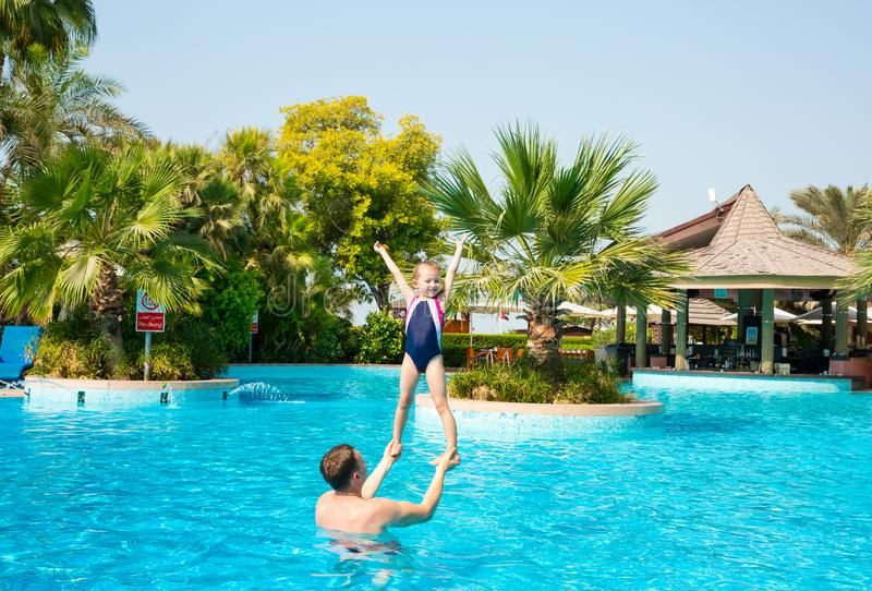 Active father teaching his kid daughter to swim in pool on tropical resort. Summer vacations and sport concept.  stock photos