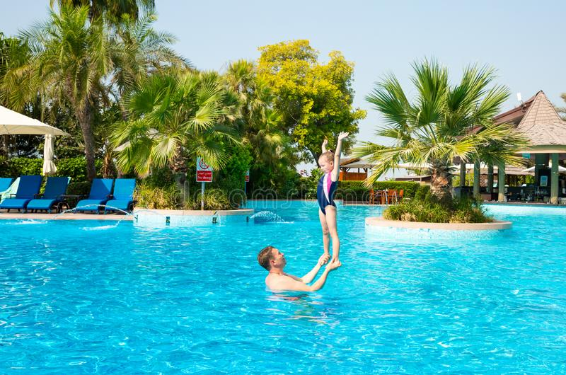 Active father teaching his kid daughter to swim in pool on tropical resort. Summer vacations and sport concept. Active father teaching his kid daughter to swim royalty free stock photo
