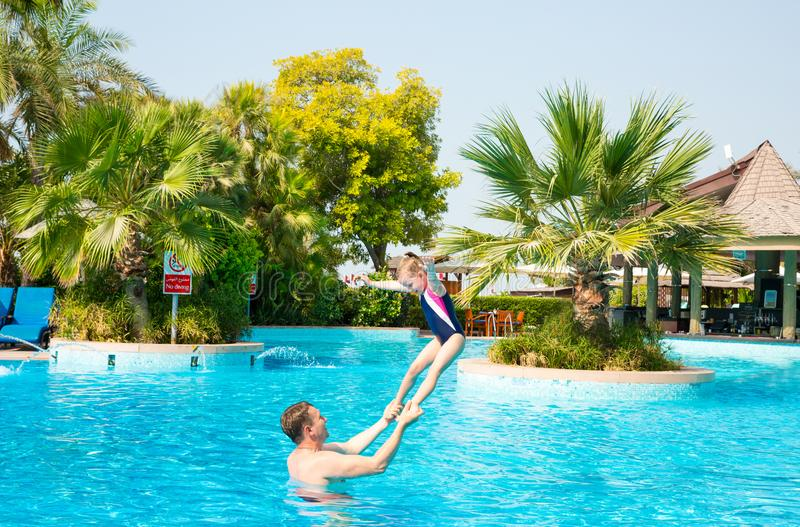 Active father teaching his kid daughter to swim in pool on tropical resort. Summer vacations and sport concept. Active a father teaching his kid daughter to swim royalty free stock photo