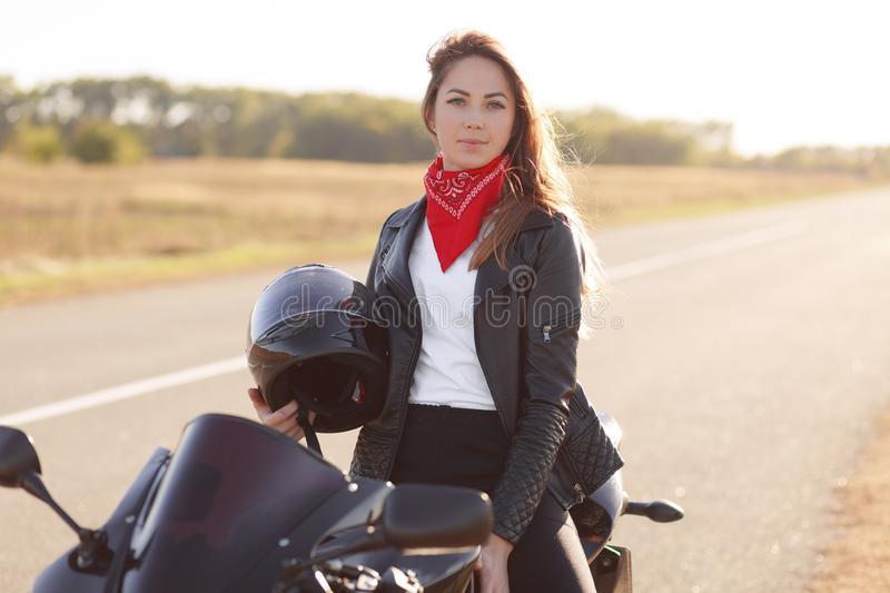 Active female driver sits on black fast motobike, holds helmet, wears leather jacket and red bandana, covers long destination, loo. Ks directly at camera, feels royalty free stock photo