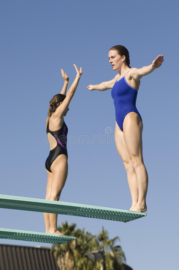 Active Female Swimmers On Diving Board royalty free stock photography