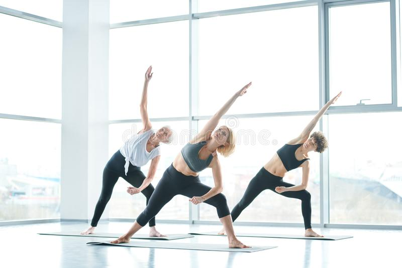 Yoga in gym. Active females raising right arms and looking at them while standing on mats during fitness or yoga practice royalty free stock photo
