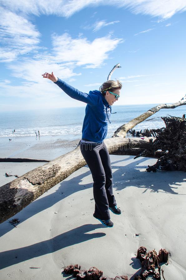 Active fit woman jumps off a large piece of driftwood on the beach of Hunting Island State Park stock image