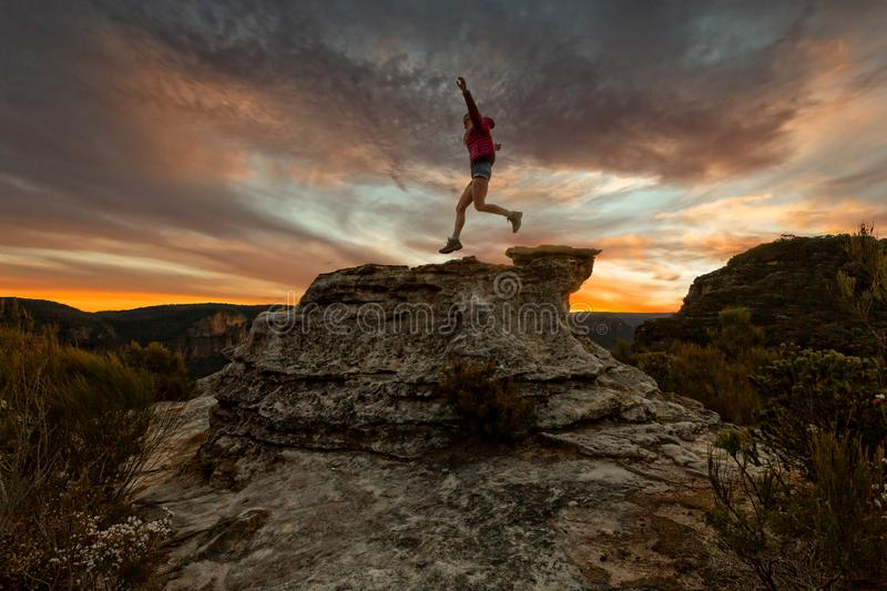 Active woman jumping on mountain cliffs at sunset stock photo