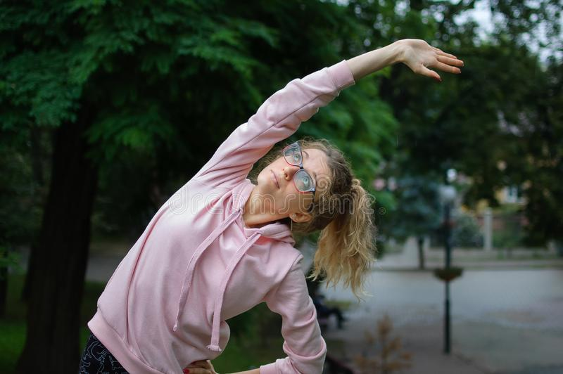 Active fitness woman in pink clothes and eyeglasses is stretching outdoor in the park during spring or summer morning. Healthy lifestyle concept royalty free stock photography