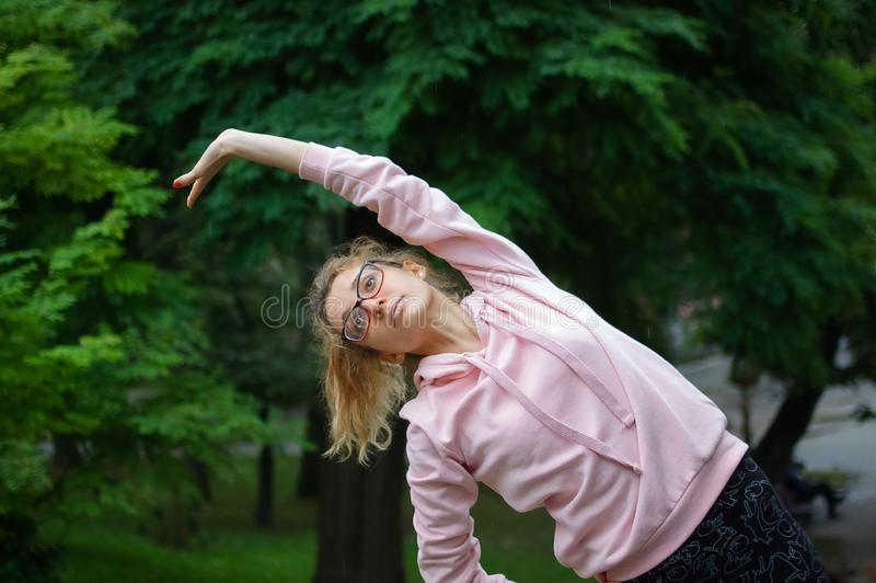 Active fitness woman in pink clothes and eyeglasses is stretching outdoor in the park during spring or summer morning. Healthy lifestyle concept stock photos