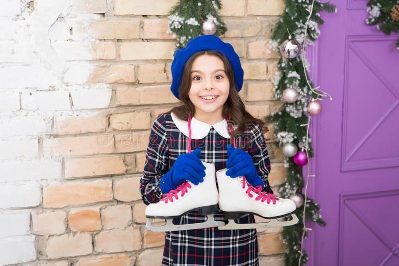 Active and fun. Professional skating equipment. Small child hold figure skates. Small girl with pair of skates. Adorable stock images