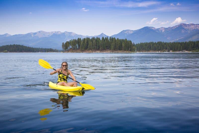 Active, geeignete Frau, die auf einem schönen Mountainsee Kayak fährt stockfotografie