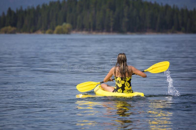 Active, geeignete Frau, die auf einem schönen Mountainsee Kayak fährt lizenzfreie stockbilder